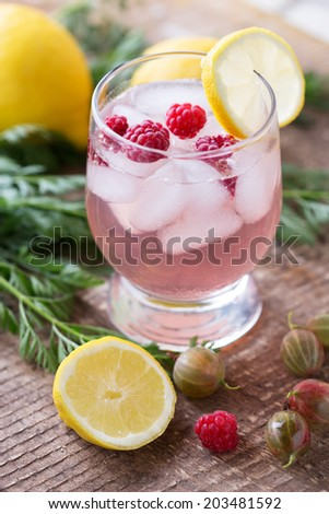 Summer drink with berries and ice in glass on wooden background. Selective focus, vertical. - stock photo