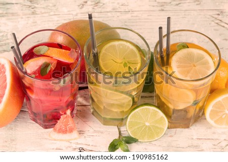 Summer drinks on wooden table. Ice team with fruits. - stock photo