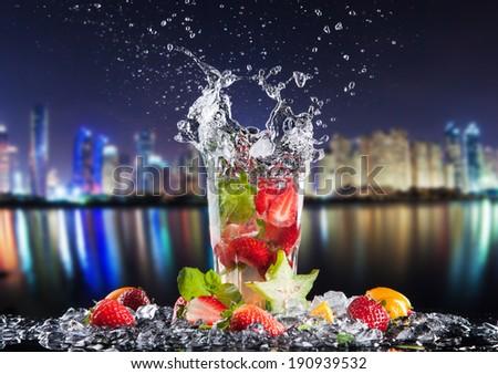 Summer drinks splashing, with blur night modern city on background - stock photo