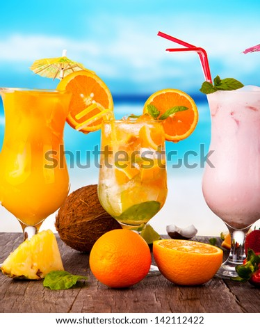 Summer drinks with blur beach on background - stock photo