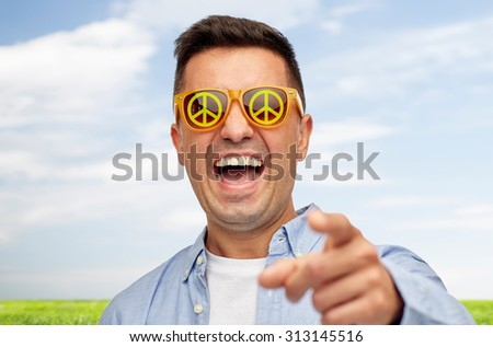 summer, ecology, emotions and people concept - face of laughing middle aged man in sunglasses with green peace symbol pointing finger on you over blue sky and grass background - stock photo