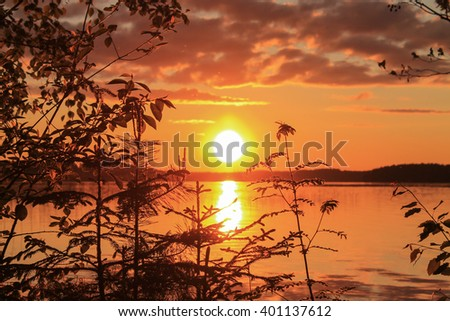 Summer evening and sunset. Its mid-summer and the sun goes down the horizon - stock photo
