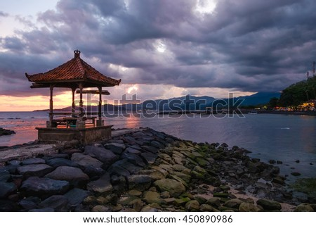 Summer evening sea view sunset with traditional Bali pavilion silhouette in front. Beautiful sea view pavilion at sunset. Romantic sunset in Bali with pavilion in front view. Summer night sunset, Bali