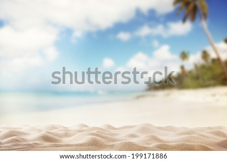 Summer exotic sandy beach with blur palms and sea on background - stock photo