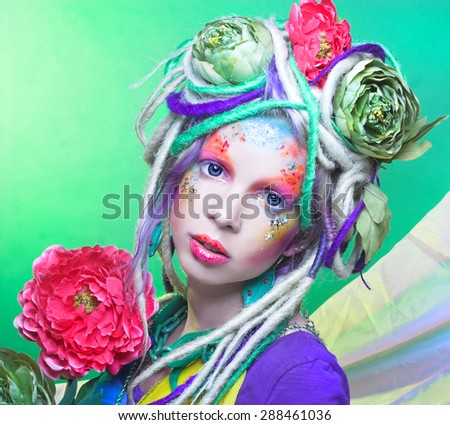 Summer fairy. Young woman in artistic image and with flowers in hair. - stock photo