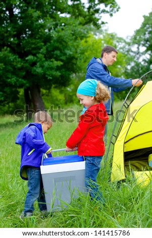 Summer, family camping - lovely sister and brother have a refrigerator with father near camp tent. Vertical view - stock photo