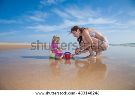 summer family of two years blonde baby pink and yellow swimsuit sitting on water with brunette woman mother in bikini with red plastic bucket at sea shore beach sand