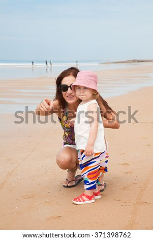 summer family of two years old blonde baby with pink hat white shirt and colorful trousers with brunette woman mother pointing at beach sand in Cadiz Andalusia Spain - stock photo