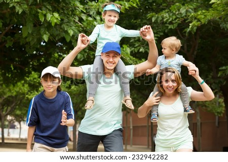 Summer family portrait of parents and kids outside - stock photo