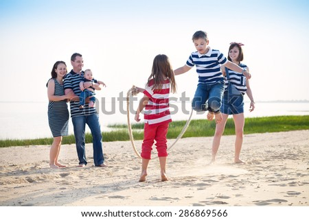 Summer family vacation - boy playing with skipping rope on the beach