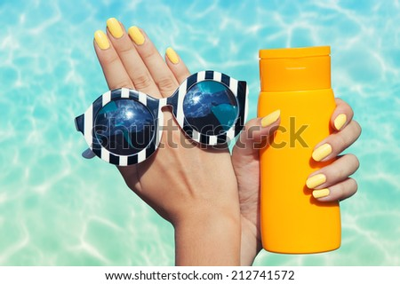 Summer fashion and beauty hand care concept, woman at the pool holding sunglasses and sunscreen lotion  - stock photo