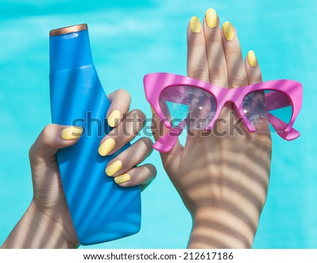 Summer fashion and beauty hand care concept, woman holding sunglasses and sunscreen lotion  - stock photo