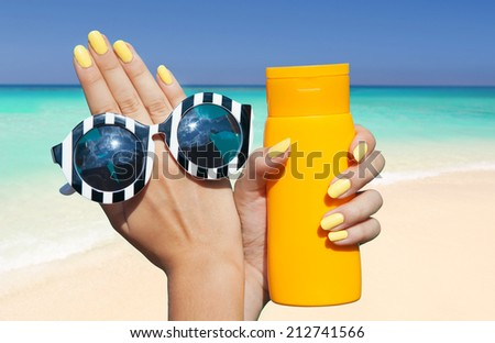 Summer fashion and beauty hand care concept, woman on the beach holding sunglasses and sunscreen lotion  - stock photo