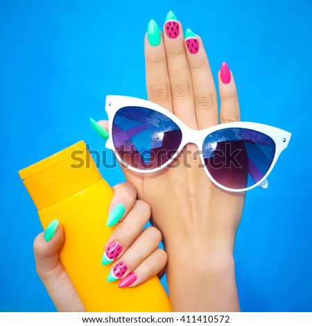 Summer fashion and beauty hand care concept, woman with watermelon gel nails holding sunglasses and sunscreen lotion