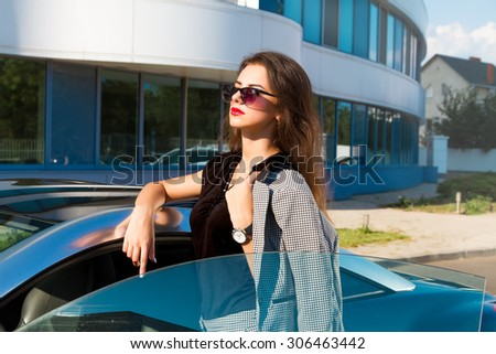 Summer fashion close up portrait of Beautiful young business woman opened her blue sport luxury car at urban modern background.Fashionable young woman posing outside in a city street. Summer Fashion. - stock photo