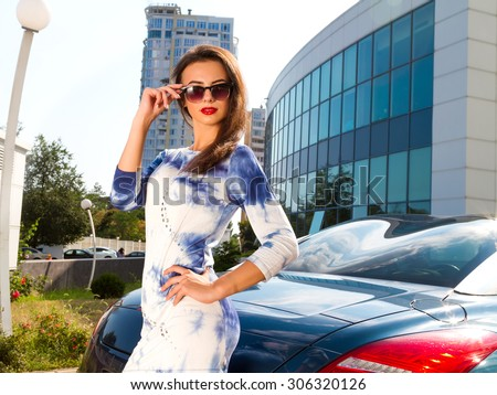 Summer fashion close up portrait of Beautiful young woman with blue sport luxury car with urban modern background.Pretty young woman wearing white trendy dress and black retro sunglasses,with red lips - stock photo