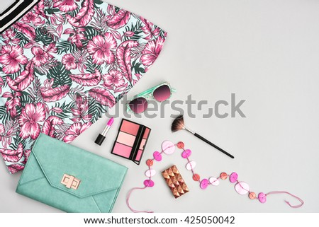 Summer fashion.Girl clothes accessories set.Woman essentials. Cosmetics, makeup.Stylish handbag clutch, dress, necklace, sunglasses .Unusual overhead summer outfit, summer top view - stock photo