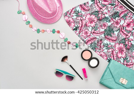 Summer fashion.Girl clothes accessories set.Woman essentials. Cosmetics, makeup.Stylish handbag clutch, dress, hat, necklace, sunglasses .Unusual overhead summer outfit, summer top view on pink - stock photo