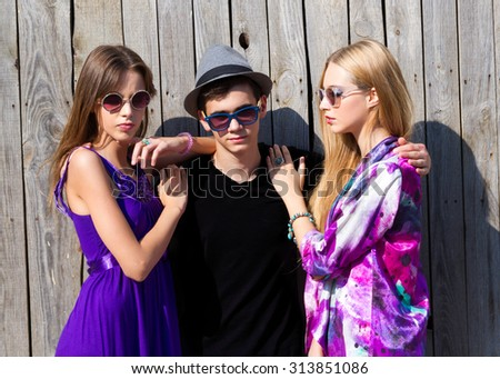 Summer fashion image of beautiful thee young  friends posing.Man and two woman around he at wooden wall background.Love story about a man and two women - concept of a love triangle.Lovely Couple.  - stock photo