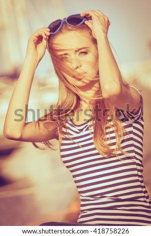 Summer fashion. Portrait girl in blue heart shaped sunglasses enjoying summer breeze at sunset in marina - stock photo