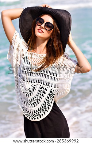 Summer fashion portrait of beautiful woman enjoy windy sunny day near ocean, vacation style. Young stylish girl wearing black romper vintage hat and big sunglasses, bright colors. - stock photo