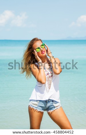 Summer fashion portrait of young pretty blonde woman with tanned fit sexy body, wearing white t-shirt, denim shorts and stylish round sunglasses, posing at tropical island beach with clear blue water