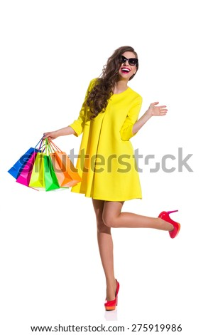 Summer Fashion Shopping. Happy elegance young woman in red high heels and yellow mini dress standing on one leg and holding colorful shopping bags. Full length studio shot isolated on white. - stock photo