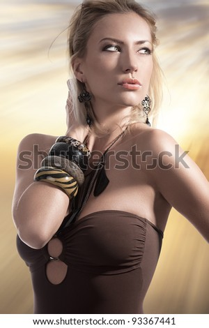 summer fashion shot of a beautiful blonde girl posing in a brown swimsuit and wearing fashion accessories - stock photo