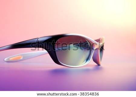 Summer - fashionable sunglasses on color background under sun light - stock photo