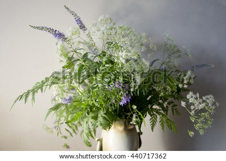 Summer field plants in a vintage vase on light backdrop. Lush green, white and purple flowers in a bouquet.  - stock photo