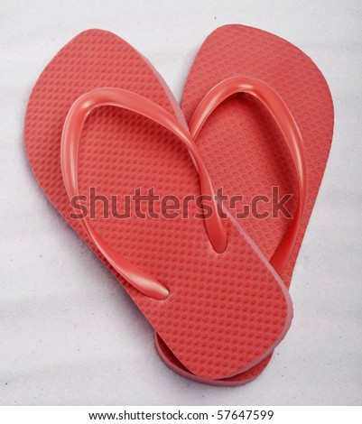 Summer Flip Flop Sandals in a Heart Shape on a Sand Background. - stock photo