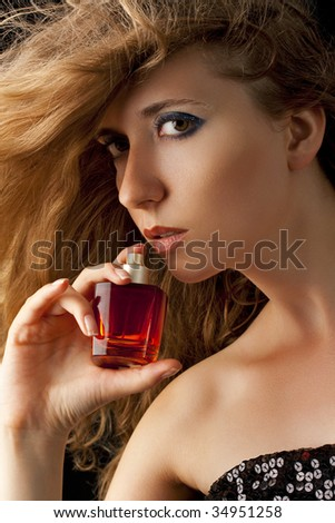 summer fragrance; beautiful woman holding  bright red perfume bottle - stock photo