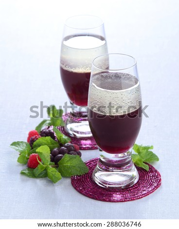 Summer fruit cocktail layered of red raspberry blackberry currant with mint in a glass on a blue tablecloth - stock photo