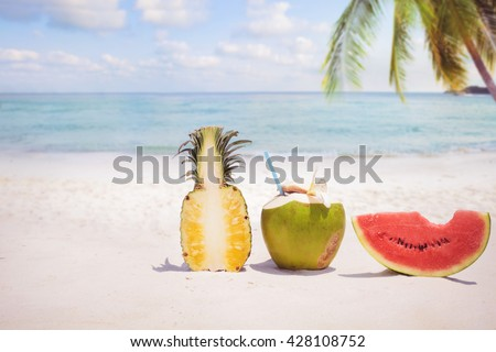 Summer fruit concept with coconut cocktial, watermelon and pineapple on sandy tropical beach - stock photo