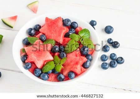 Summer fruit salad of watermelon and blueberries. Slices of watermelon in the shape of a star. Top view - stock photo