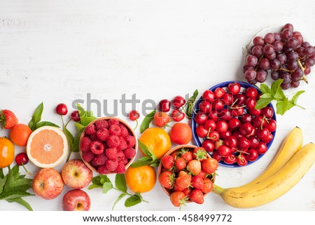 Summer fruits and berries (strawberries, cherries, raspberries, oranges, grapes, persimmon) on a white table, top view, space for text, selective focus - stock photo