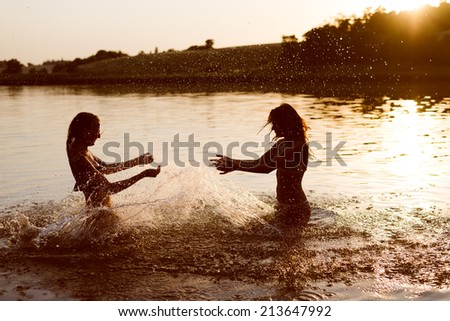 summer fun: filtered image of 2 beautiful young woman or teenage girls best friends having fun and splashing water in river or lake at sunset on sunny outdoors copy space background - stock photo
