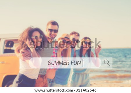 Summer fun. Group of cheerful young people embracing and looking at camera while walking along the beach  - stock photo