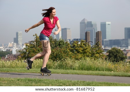 Summer fun in London for beautiful young sexy woman, roller skating through the park with a big happy smile, against the cityscape backdrop of London, England United Kingdom. - stock photo