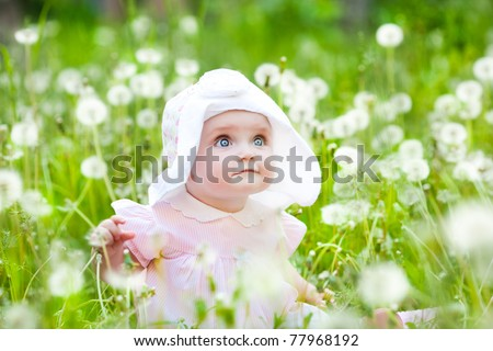 Summer fun, sweet little girl, sitting and blowing dandelion on the meadow - stock photo