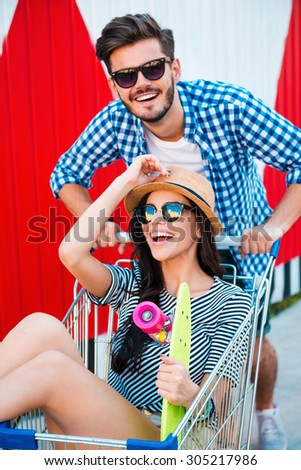Summer fun. Top view cheerful young woman sitting in shopping cart while her boyfriend pushing it - stock photo