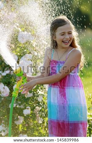Summer fun, watering flowers - lovely girl has fun watering flowers in the garden - stock photo
