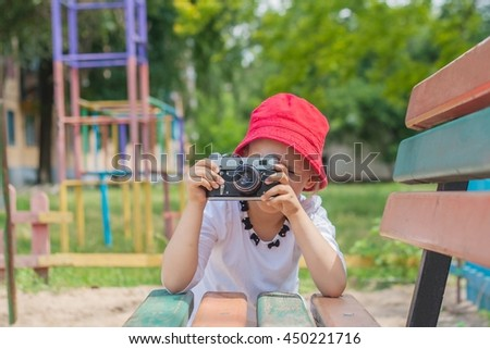 Summer games . Little girl with photo camera .  Summer games on air . Clever child. A hobby for children . Technology retro . Child with camera . Little girl photographing - stock photo
