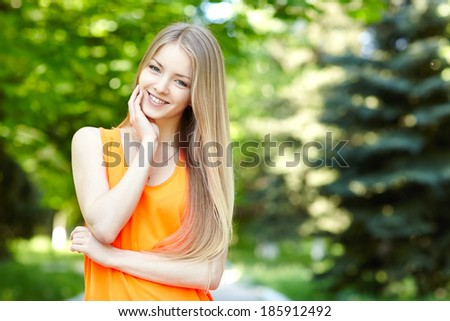 Summer girl portrait.  Closeup of a woman smiling happy on sunny summer or spring day outside in park. Pretty young woman outdoors. - stock photo