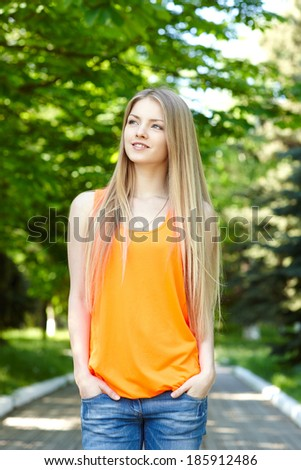 Summer girl portrait.  Pensive casual woman standing with hands in pockets smiling happy on sunny summer or spring day outside in park, looking away. Pretty young woman outdoors. - stock photo