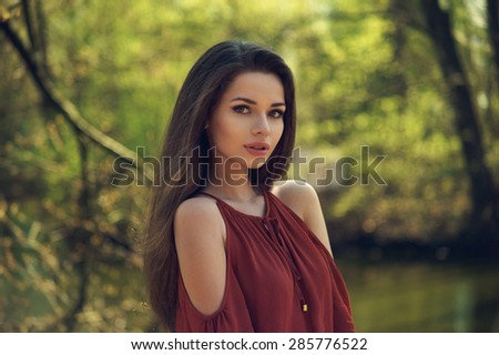 Summer girl portrait. Pretty caucasian woman on sunny summer or spring day outside in park - stock photo
