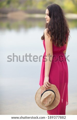 Summer girl portrait. Young woman smiling happy on summer or spring day outside in park by lake - stock photo