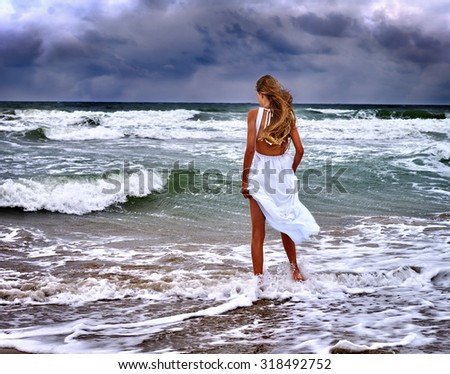 Summer girl sea.  Woman goes at water on coast.