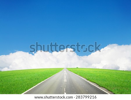Summer grass, sky and road landscape. Endless asphalt lane through the green field and clouds till the horizon