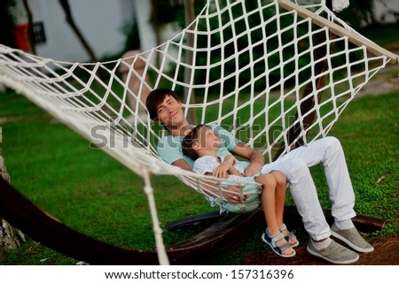 summer green park father and son are in a large hammock - stock photo